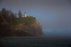 Lighthouse on cliff above foggy calm ocean Stock Images