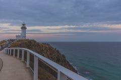 Lighthouse on cliff against cloudy sky stock photos