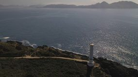 Lighthouse on a cliff on the background of the ocean top view. 4k video from the drone stock footage