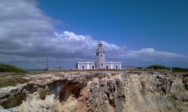 Lighthouse and cliff with clouds stock images