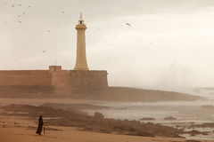 Lighthouse on the cliff in Rabat. Lighthouse on the cliff with fortifications in Rabat with storm, Morocco stock photography
