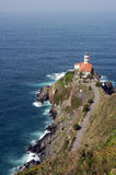 Lighthouse on cliff by sea Stock Images