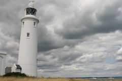Lighthouse and cloudy sky. A tall white lighthouse on a cloudy sky background Royalty Free Stock Photography