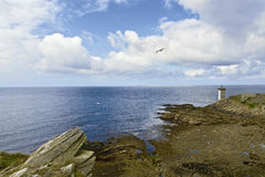 Lighthouse by the coast in Britain with clouds Royalty Free Stock Images