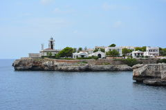 Lighthouse on the coast of Menorca. Lighthouse and village on the coast of Menorca, by Ciutadella in Cala des frares Stock Photography
