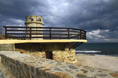 Lighthouse on the coast. Taken on a sunny day on a background of dark rain clouds. Bulgaria Stock Photos