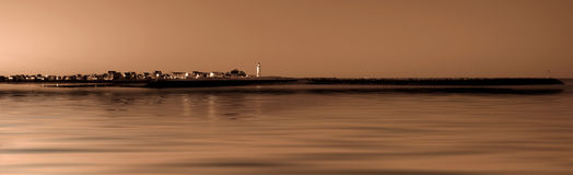 Lighthouse Coastline. In warm tones and stll water Stock Images