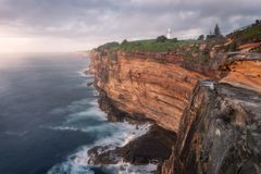 Lighthouse and Coastline. Formidable coastline of Sydney, Australia with the Macquarie Lighthouse. The sunrise highlights the sandstone cliffs. The oceans royalty free stock image