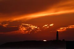 Lighthouse with colorful sunset with sun on skyline stock photography