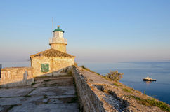 Lighthouse on the corfu fortress. Ship and sea behind Stock Photography