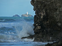 Lighthouse, Cornwall, England. The famous coast of Cornwall, England with a lighthouse on a solitary rock in the background stock photo