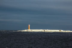 Lighthouse in dark sky. Outside was cold -15degress in Latvia, bolderaja breakwater Royalty Free Stock Photos