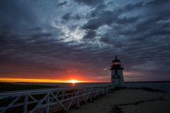 Lighthouse at dawn in Nantucket. June 25, 2017 Nantucket Massachusetts - A Light house stands at dawn under an amazing skyscape as the sun rises Royalty Free Stock Photo