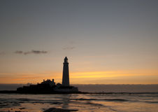 Lighthouse at Dawn. A silhouetted lighthouse stands guard over rocks to prevent passing boats and ships coming to grief on them at dawn stock photography