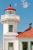 Lighthouse Detail. Close up of historic Mukilteo Lighthouse with white tower and house and red roof against brilliant blue sky. Lens clearly visible. Mukilteo Stock Images