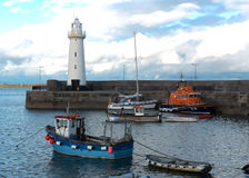 The lighthouse at Donaghadee in County Down with Lifeboat. The lighthouse at Donaghadee in County Down with the RNLI Lifeboat and other vessels on a calm summer Stock Images
