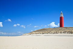 Lighthouse in the dunes at the beach. With blue sky Royalty Free Stock Photo