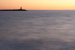 Lighthouse at dusk. Lighthouse on the end of a pier at sea photographed at dusk. Guiding the ships safely into the harbor. Smooth motion blurred ocean water stock photography