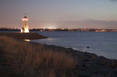 Lighthouse at dusk. Lighthouse protects rocky beach from danger Stock Photography