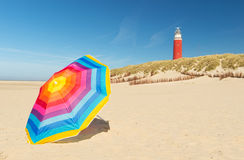 Lighthouse on Dutch wadden island Texel. Lighthouse with colorful parasol in front on Dutch wadden island Texel stock photos