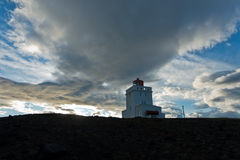 Lighthouse at Dyrholaey rock at sunset with dramatic sky Royalty Free Stock Photography