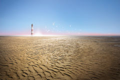 Lighthouse at Ebb Tide Coast and Sea Gulls. Lighthouse on a dried ocean, low tide coast, with sea gulls over the sunset and tracks of waves in the sand Royalty Free Stock Image