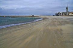 Lighthouse on edge of the beach Stock Photography