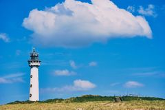 Lighthouse Egmond aan Zee, Netherlands. White lighthouse in Egmond aan Zee on a green meadow with a big white cloud above and nice blue sky royalty free stock photography