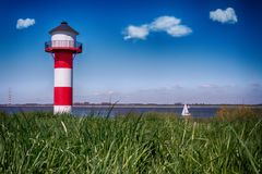 Lighthouse Elbe Germany With Blue Sky And Clouds. Water And Sail Boat In Background Royalty Free Stock Photography