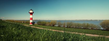 Lighthouse Elbe Germany - Panorama. Lighthouse Elbe Germany - Panoramic View With Gras In Foreground And Water In Background Stock Photo