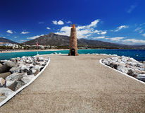 Lighthouse at the end of breakwater in the Puerto Banus in Marbella, Spain Royalty Free Stock Images