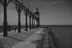 The lighthouse at the end of the pier royalty free stock photo