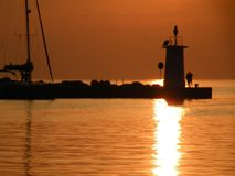 Lighthouse at the end of the pier of stones, sunset over the Adriatic Sea, Croatia, Europe.Orange, calm sea, silhouette, reflectio stock photos