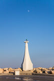Lighthouse At The Entrance To The Marina On A Background Of Blue Sky With The Moon Stock Images