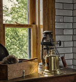 Lighthouse equipment. 1920s blowtorch, oil lantern and feather dusters, sit in front of a lighthouse window.  Split Rock Lighthouse, Two Harbors, Minnesota Stock Image