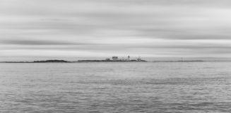 Lighthouse facing stormy seas during a fall afternoon in Maine royalty free stock images