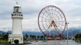 Lighthouse and ferris wheel on the background of mountains royalty free stock photos
