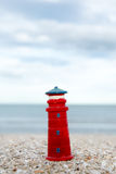 Lighthouse figure on the beach in the evening Stock Images