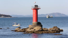 Lighthouse with fishing boat stock video footage