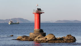 Lighthouse with fishing boat. In the sea stock video footage