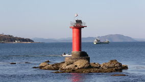 Lighthouse with fishing boat. In the sea stock video