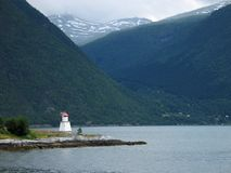 Lighthouse in fjord. Scenic view of lighthouse or beacon with mountainous fjord in background Royalty Free Stock Images