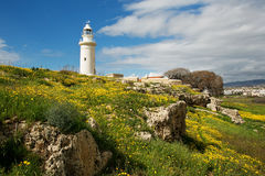 Lighthouse on the flowered meadow. White lighthouse surrounded by yellow flowers and scenic sky with clouds royalty free stock image