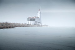 Lighthouse in the fog is on the pier into the sea. mystical land Royalty Free Stock Image