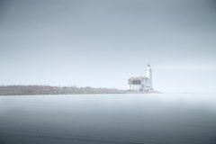 Lighthouse in the fog is on the pier into the sea. mystical land Stock Image