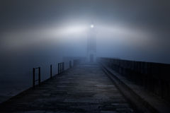 Lighthouse in a foggy night Stock Photos