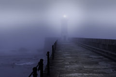 Lighthouse in a foggy night Stock Images
