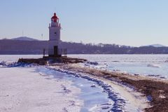Lighthouse on the foreland. Seascape on a cold winter day. The water is covered with ice and snow. In the distance is an old lighthouse, a round white tower Royalty Free Stock Photos