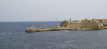 La Valletta Lighthouse and the Fort. Lighthouse and fortress of the entrance in the harbour of Valletta,Malta Royalty Free Stock Image