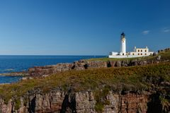 Deep blue sky with lighthouse. Rua Reidh lighthouse with keepers house on a rocky, grassy coastline with blue sky royalty free stock images